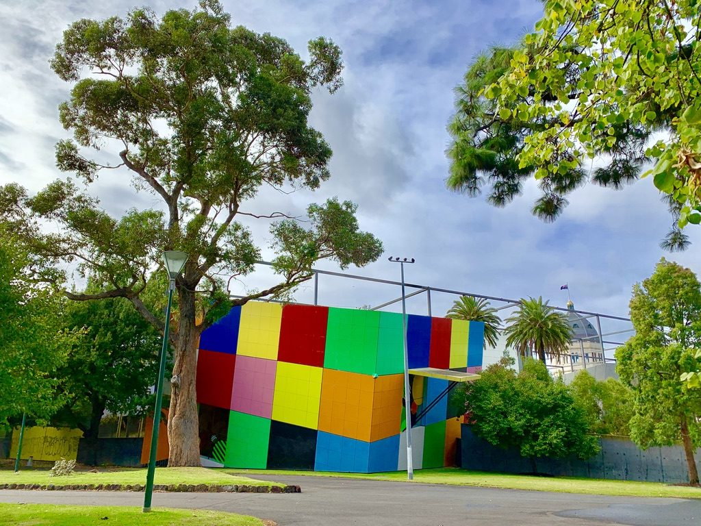 large multi-coloured cube and trees